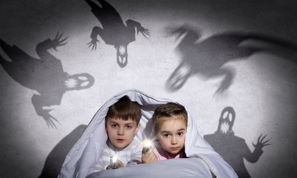 Two little kids with flashlight under blanket