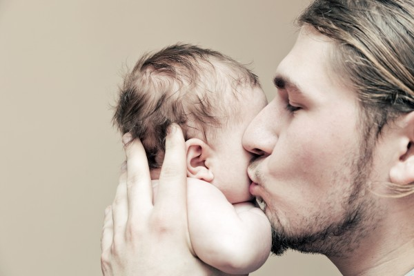 Father with his young baby cuddling and kissing him on cheek. Pa
