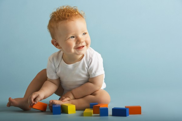Full length of baby boy playing with building blocks isolated on