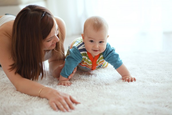 Mother with her baby playing on a carpet at home