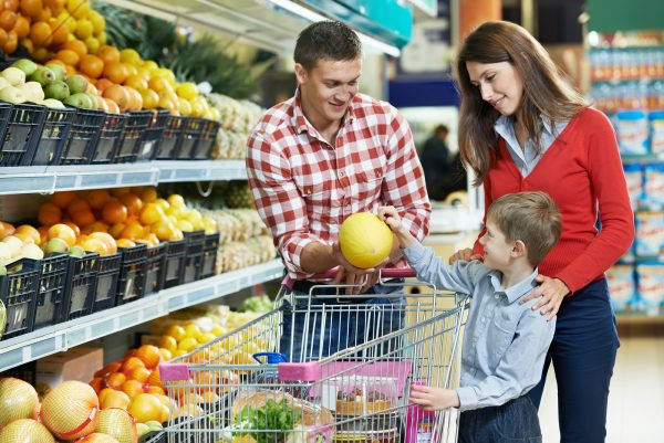 woman with man and child choosing melon fruit during shopping at