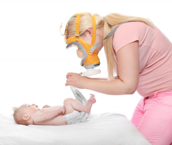 Diaper changing - hygiene concept. Young mother solving an smell