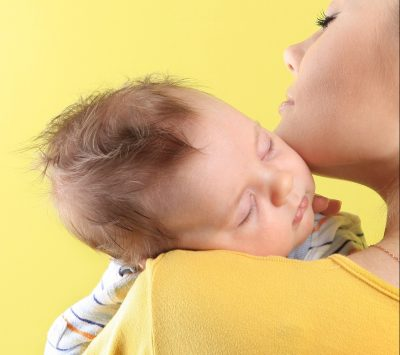 young mother with baby sleeping on shoulder